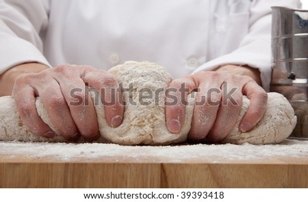 hands kneading bread dough on a cutting board - stock photo