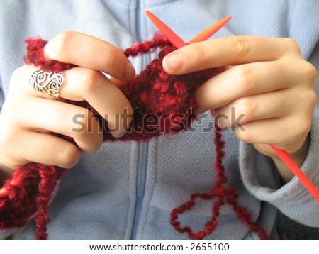 Hands knitting a red scarf on blue background - stock photo