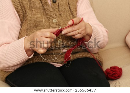 Hands knitting close-up Elderly woman knitting with red wool. - stock photo