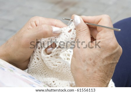 hands knitting in a square