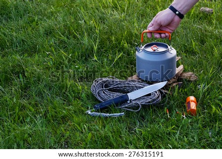 Hands lighting the fire at a campsite for cooking and making tea or coffee. Outdoor food items set. Travel, tourism and camping equipment. Picnic on the nature. Summer BBQ tools. Campfire kettle.
