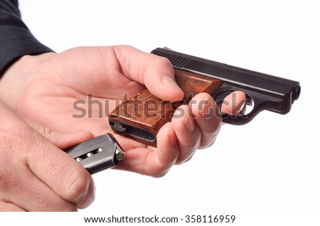 Hands loading a gun on a white background - stock photo