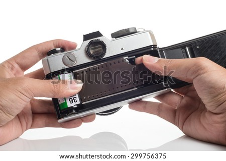 Hands loading film into SLR camera - stock photo