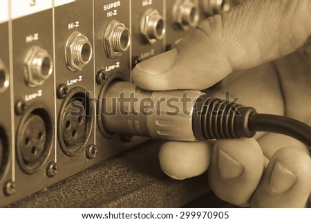 Hands-maker to control the plug - Jack Connector XLR connection with, mixer amplifier. On background old brown - stock photo