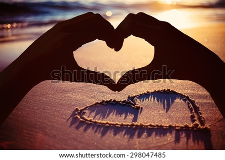 Hands making heart shape on the beach against one heart drawn in the sand - stock photo