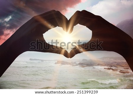 Hands making heart shape on the beach against sunrise over magical sea - stock photo