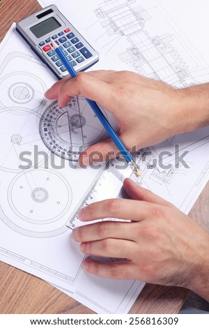 Hands male engineer next to the drawings, a calculator and a protractor. Complex engineering drawings. Workplace mechanical engineer. Students of technical school. The practical work of the student. - stock photo