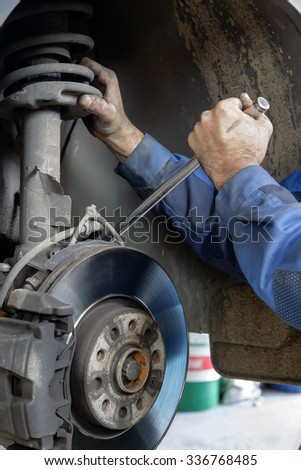 Hands mechanics repaired the brakes on a passenger car - stock photo