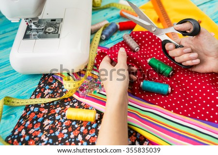 Hands mistress seamstress made a beautiful bright fashionable clothes. The crosslinking parts of the pattern. Work place. Top view. Light Textile industry creative moments
