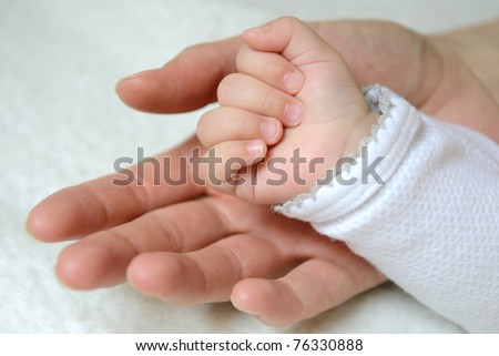 Hands - mother and baby - stock photo