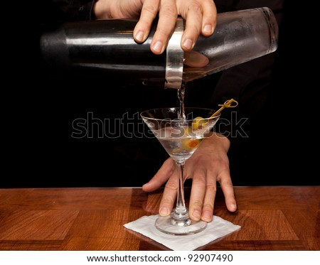 hands of a bartender holding a shaker pouring a drink into a martini glass - stock photo