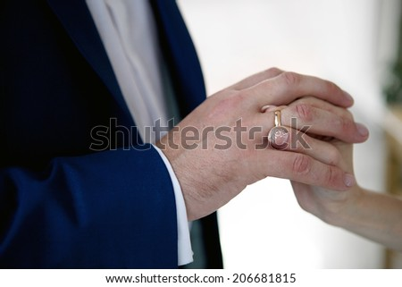hands of a bride and a groom, woman putting a wedding ring on the finger of her groom - stock photo