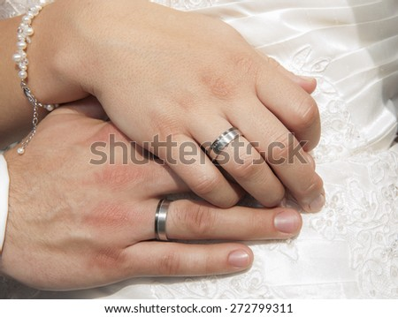 Hands of a bride and groom at a wedding ceremony showing rings - stock photo