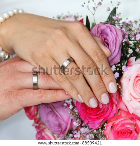 Hands of a bride and groom with wedding rings - square