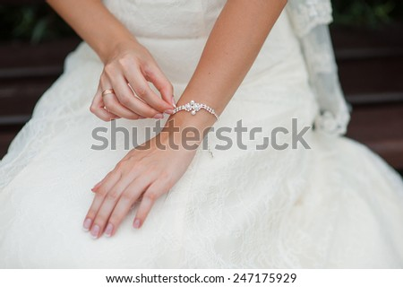 hands of a bride with a decoration bracelet. - stock photo