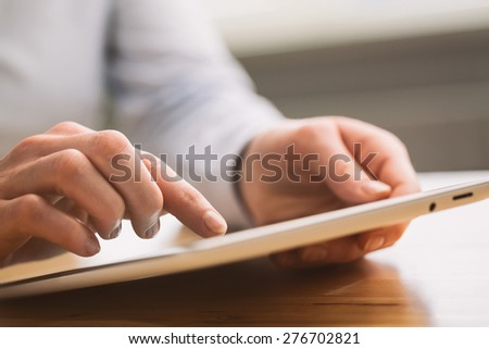 Hands of a business woman hold and use a tablet computer. Shallow DOF, focus on the index finger. - stock photo