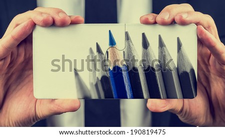 Hands of a businessman holding two puzzle pieces depicting a greyscale image of colored pencils with one blue pencil standing out from the others in a leadership and individuality concept. - stock photo