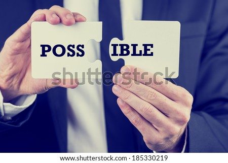 Hands of a businessman in a suit holding puzzle pieces with the word Possible spread over the two sections conceptual of problem solving and overcoming challenges, retro effect faded look. - stock photo