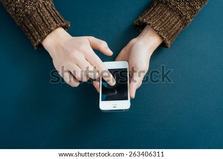 Hands of a businesswoman using a smartphone - stock photo
