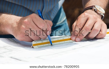 Hands of a busy young engineer as he works on  construction project plans using a pen and scale ruler - stock photo