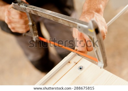 hands of a carpenter or woodworker using a hacksaw to cut a metallic bar during the construction of a wooden piece of furniture - stock photo