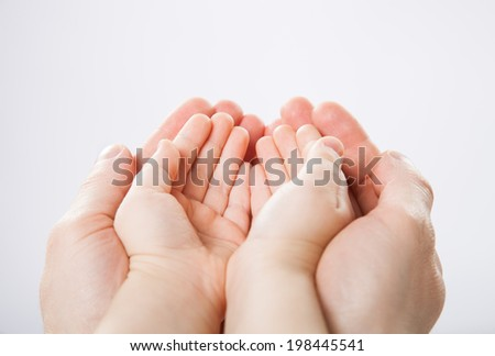 Hands of a child and a father holding each other - stock photo