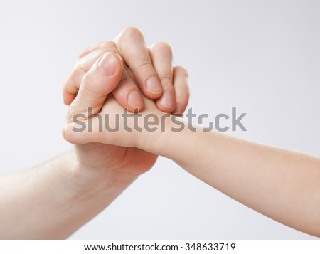 Hands of a child and a father holding together, closeup shot