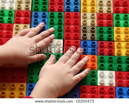 Hands of a child building blocks, lining them up in a row. Useful for a building concept or exploring concepts. - stock photo