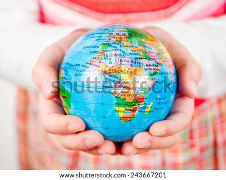 Hands of a child holding a globe - stock photo