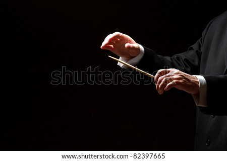 Hands of a conductor isolated on black background - stock photo