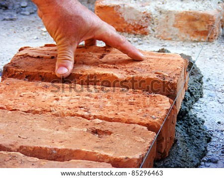 Hands of a construction mason worker bricklayer - stock photo