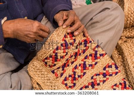Hands of a craftsman weaving handicraft items made of jute - stock photo