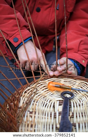 Hands of a craftsman working on a wicker basket