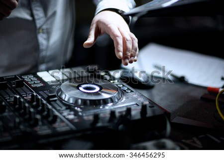 Hands of a D.J. mixing recorded music at event - stock photo