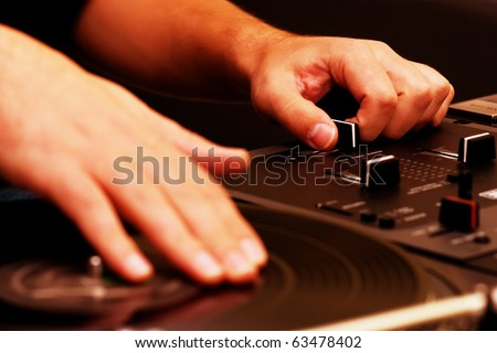Hands of a disk jockey playing the music on the turntable and top-class mixing controller - stock photo