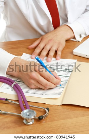 Hands of a doctor filling RX prescription, documents at the desk - stock photo
