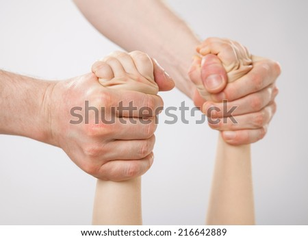 Hands of a father holding a child and swinging him (her), closeup shot - stock photo
