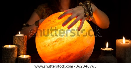 Hands of a female fortune teller, a shining crystal ball and candles