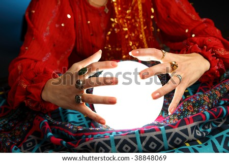 hands of a fortune-teller working with a shining crystal ball - stock photo