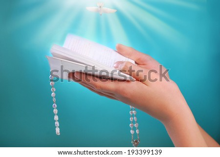 hands of a girl going to the first holy communion holding prayer book with rosary on blue background - stock photo
