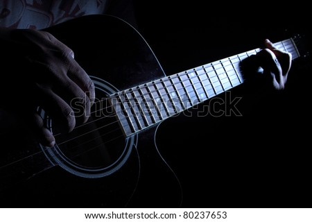 Hands of a guitarist playing guitar at night - stock photo