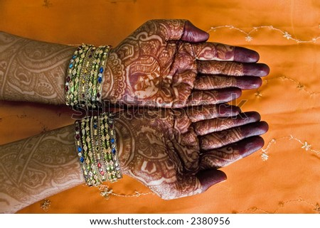Hands of a Indian bride with henna design and bangles - stock photo