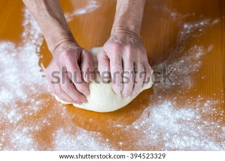 Hands of a male baker making bread on the table
