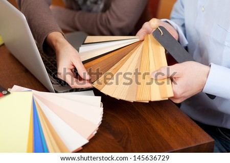 Hands of a man and woman choosing timber samples for the house during a renovation project - stock photo