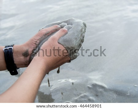 Hands of a man holding sand and let it slips through his hands at the beach which was gathered from the ground and shows connection of men and nature. Beach and sea are in the back ground.