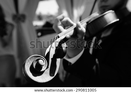 Hands of a man on the strings of a violin - stock photo