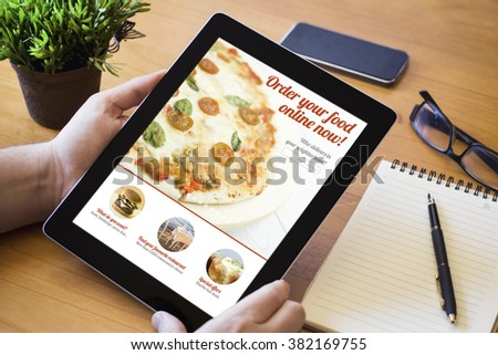 hands of a man ordering pizza with a device over a wooden workspace table. All screen graphics are made up. - stock photo