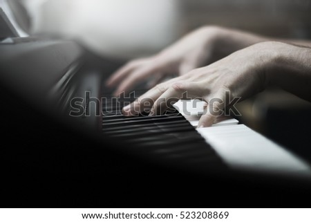 Hands of a man playing the piano with soft atmosphere - closeup