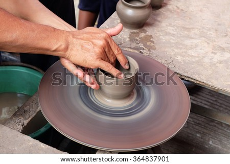Hands of a man potter creating an earthen jar on the circle from soft clay. Closeup processing shaping pot. - stock photo
