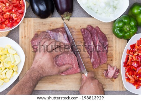 Hands of a man preparing meat and vegetables in a kitchen slicing lean meat on a wooden board with diced zucchini, tomato and onion and whole eggplant and green bell pepper - stock photo
